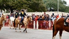 San Antonio, Texas de V.S. - 3 Februari 2018: De vrouwen op paarden berijden voorbij historische Alamo tijdens parade stock footage
