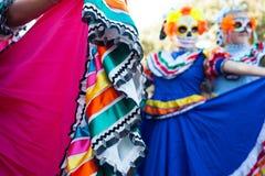 SAN ANTONIO, TEXAS - OKTOBER 28, 2017 - nära övre detalj av den traditionella klänningen och suddig bakgrund av flickor med maske arkivbild