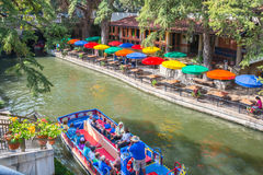 San Antonio Texas River Walk and Boat Cruise. SAN ANTONIO, TEXAS - SEPT 25, 2014: Tourists taking a river cruise along River Walk with colorful umbrellas of stock photos