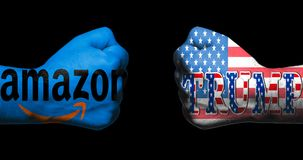 SAN ANTONIO, TX - APRIL 9, 2018 - Amazon logo and Trump with US flag painted on two clenched fists facing each other/concept of co royalty free stock image