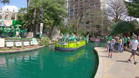 SAN ANTONIO, TX - MARCH 17, 2018 - Colorful boats with tourists visiting San Antonio Riverwalk on a sunny spring day. The river is. Colored green, celebrating stock video