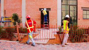 San Antonio TX - mars 6, 2017: Byggnadsarbetare i orange arbetsvästar arkivbild