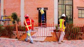 San Antonio, TX - Marzec 6, 2017: Pracownicy budowlani w pomarańczowych prac kamizelkach fotografia stock