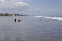 Playing in the surf Ecuador. SAN CLEMENTE ECUADOR, FEBRUARY-2013 Vacationers playing in the surf Feb 2013 in San Clemente Ecuador.San Clemente is a fishing royalty free stock photo