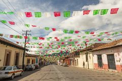 Colorful Flag Lined Street. SAN CRISTOBAL, MEXICO - NOVEMBER 27: Unidentified people on a quiet street lined with colorful paper flags or papel picado in the stock image