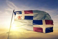 San Cristobal Province of Dominican Republic flag textile cloth fabric waving on the top sunrise mist fog. Beautiful royalty free stock photo