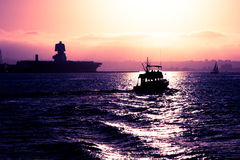 San Diego Bay Sunset. This image has been modified to amplify the colors of a sunset on the San Diego Bay. Beyond the fishing boat you can see the silhouette of stock image