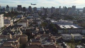 San Diego, CA/USA - circa Januari 2016: Vliegtuig die in de luchthaven met San Diego van de binnenstad op de achtergrond landen stock videobeelden