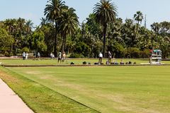 Teams of People Playing Lawn Bowling in Balboa Park. SAN DIEGO, CALIFORNIA - APRIL 28, 2017:  Teams of people playing lawn bowling in Balboa Park, which has the Stock Image