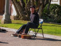 Disabled armless person plays on guitar by his toes. SAN DIEGO, CALIFORNIA - MARCH 12, 2007: Disabled armless person plays on guitar by his toes in Balboa Park Royalty Free Stock Photos