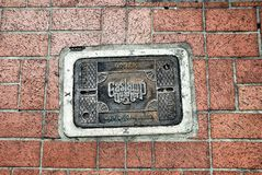 San Diego Gaslamp Quarter utility cover. San Diego Gaslamp Quarter lighting utility access, set in the brick sidewalk Royalty Free Stock Images