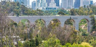 SAN DIEGO - JULY 30, 2017: Bridge and San Diego skyline with trees on foreground.  royalty free stock image