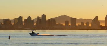 San Diego Saturday. Boat speeds across San Diego Bay in the early morning dawn. San Diego skyline in the background Royalty Free Stock Photo