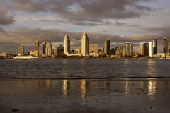 San Diego Skyline. Skyline of San Diego California at sunset under cloudy sky with tour boat sailing on bay Royalty Free Stock Photos