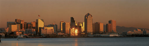 This is the San Diego skyline with the bay in front at sunset. The reflected light on the buildings is golden. Stock Images