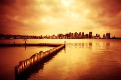 San Diego Skyline with bay and sunset. Beautiful sunset over San Diego skyline with bay and and line of wooden posts stock images