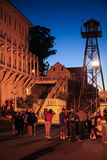 San Francisco Alcatraz Night Tour Group. Visitors wait at the boat dock on one of the special night tours of Alcatraz, with the dock guard tower looming behind Royalty Free Stock Photo