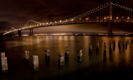 San Francisco Bay Bridge at Night. The San Francisco Bay Bridge at night with lights reflecting in the water and old piers in the foreground Stock Images