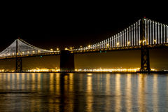 San Francisco Bay Bridge At Night. The beautiful San Francisco Bay Bridge lit with it's popular Bay Bridge Lights motion display with reflections on the water Royalty Free Stock Photo