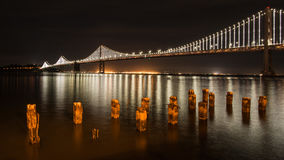 San Francisco Bay Bridge at Night with Pilings in the Foreground. The San Francisco–Oakland Bay Bridge is a complex of bridges spanning San Francisco Bay in Stock Images