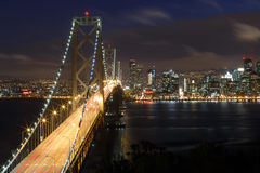 San Francisco Bay Bridge and skyline at night Stock Images
