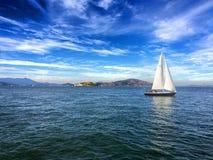 San Francisco Bay med Alcatraz och en segelbåt Royaltyfri Bild