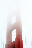 San Francisco Bay with top of Golden Gate Bridge suspension tower covered in fog Royalty Free Stock Images