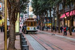 San Francisco, CA - January 3, 2016.  Trolley Number 24 approaches the busy Powell St. Station. Happy, holiday travelers and shoppers watch as Number 24 comes Stock Image