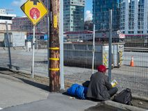 Homeless man rests outside of Caltrain station in San Francisco stock photo