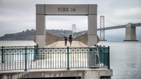 SAN FRANCISCO, CA - 2. September 2014: Pier 14 in San Francisco mit Buchtbrücke im Hintergrund Lizenzfreie Stockbilder