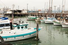 Small wooden fishing boats tied up at a pier royalty free stock image