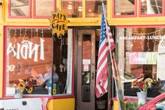 A United States flag in front of the glass of a coffee shop in San Francisco, California, Spain. stock photography