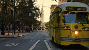 Streetcar Travels on Market Street with Ferry Building in Distance. SAN FRANCISCO - Circa October, 2016 - A yellow streetcar travels on Market Street with the stock footage