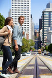San Francisco city street people students walking. San Francisco city people lifestyle. Young interracial couple students walking on city street crossing road stock photography