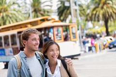 San Francisco city travel couple tourists. People lifestyle. Young interracial students on city street looking away with cable car railway system in the stock images