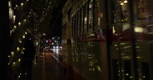A old fashioned tram at night. SAN FRANCISCO - DECEMBER 26, 2017: A old fashioned tram is riding at North Embarcadero street at night - famous tourists` stock video footage