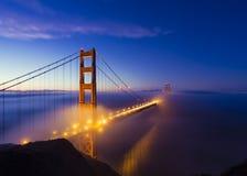 San Francisco Fog + Golden Gate Bridge. The San Francisco Golden Gate Bridge glows as the fog hugs the coast Stock Photos