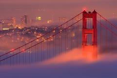 San Francisco Golden Gate Bridge in fog. Golden Gate Bridge glowing in covering fog after sunset Stock Photography