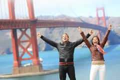 San Francisco happy people at Golden Gate Bridge. San Francisco happy people tourist couple at Golden Gate Bridge. Young attractive modern couple cheering happy Royalty Free Stock Images