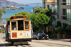 San Francisco Hyde Street Cable Car. Passengers riding one of the iconic, famous Powell & Hyde Cable Cars climbing up Hyde Street with historic Alcatraz Island Stock Photography