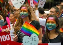 SAN FRANCISCO - JUNI 28: Två unga kvinnor med målade framsidor håller ögonen på den glade Pride Parade, Juni 28, 2015 Royaltyfri Foto