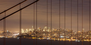 San Francisco at Night. San Francisco through the cables of the Golden Gate bridge Royalty Free Stock Photography