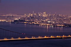 San Francisco at Night with the Golden Gate Bridge. In this image, a portion of the Golden Gate Bridge serves as foreground interest for a panorama of the city Stock Photos