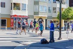 San Francisco Road Race Vendor på gatahörn som racerbilar kör vid honom arkivbild