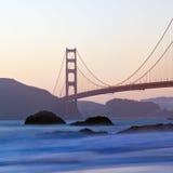 San Francisco's Golden Gate Bridge at Dusk. Brilliant blurred water, rugged rocks and a pastel sky frame the Golden Gate Bridge at Sunset Stock Photo