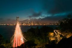 San Francisco Skyline di notte con traffico attraverso il ponte della baia immagini stock libere da diritti