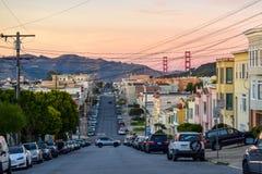 San Francisco Skyline med den bostads- grannskapen, den krokiga gatan och Golden gate bridge på solnedgången royaltyfria bilder