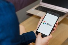 SAN FRANCISCO, US - 22 April 2019: Close up to female hands holding smartphone using Google Alerts Service application, San. SAN FRANCISCO, US - 22 April 2019 royalty free stock photography