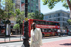 San Francisco, USA - 12 June 2010. Representative black man in a white suit walking down the street and smoking a cigar. Stock Photography