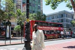 San Francisco USA - 12 Juni 2010 Representativ svart man i en vit dräkt som går ner gatan och röker en cigarr Arkivbild
